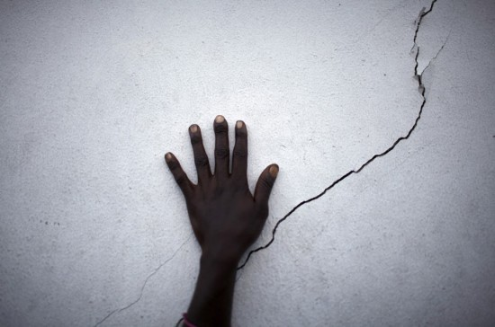 hand near a crack on a wall
